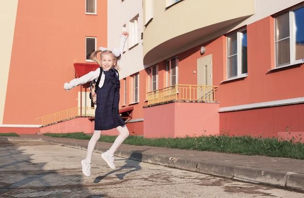 Gelukkig blond schoolmeisje gaat op zonnige dag naar school