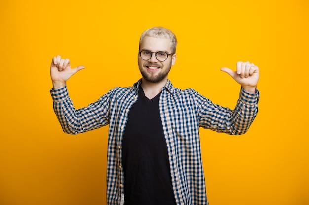 Gelukkig blonde blanke man wijzend op hem dragen van een bril en baard op een geel
