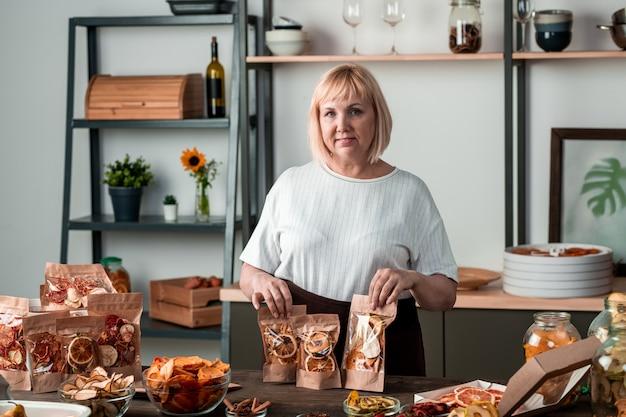Gelukkig blonde huisvrouw in wit t-shirt met pakketten zelfgemaakte gedroogde vruchten bereid als cadeau voor vrienden of voorzieningen voor de winter