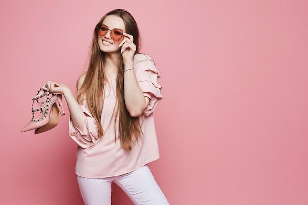 Gelukkig blonde modelmeisje met een glanzende glimlach in beige blouse en modieuze roze zonnebril die modieuze schoenen houden en bij de roze geïsoleerde achtergrond stellen