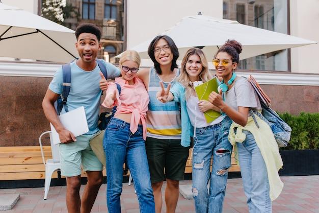 Gelukkig blonde vrouw draagt jeans met gaten poseren buiten in de buurt van lachende vrienden. openluchtportret van tevreden studenten die laptop en rugzakken in ochtend houden.