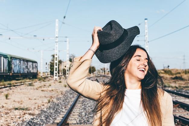 Gelukkig blonde vrouw haar hoed opstijgen in een verlaten treinstation.