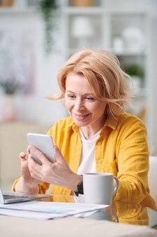 Gelukkig blonde vrouw met smartphone kijken door werkplan zittend door bureau in thuisomgeving tijdens quarantaine