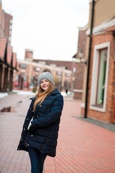 Gelukkig blonde vrouw met zwarte winterjas en gebreide muts poseren op straat in kiev