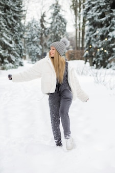 Gelukkig blonde vrouw spelen met sneeuw in het bos