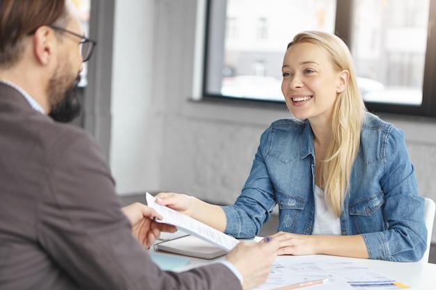 Gelukkig blonde vrouwelijke manager heeft gesprek met mannelijke collega