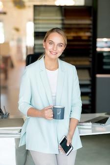 Gelukkig blonde zakenvrouw in slimme vrijetijdskleding met thee bij pauze door haar werkplek