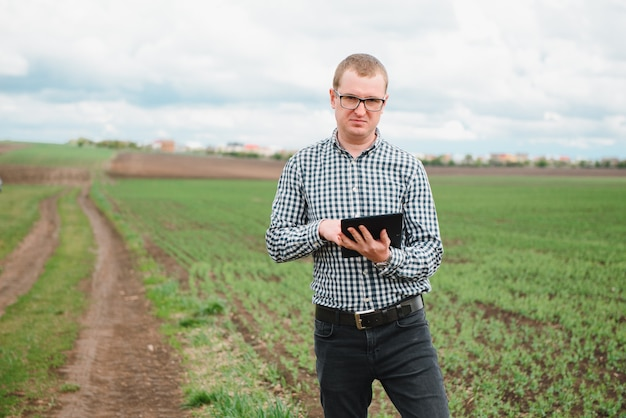 Gelukkig boer in de velden met een laptopcomputer