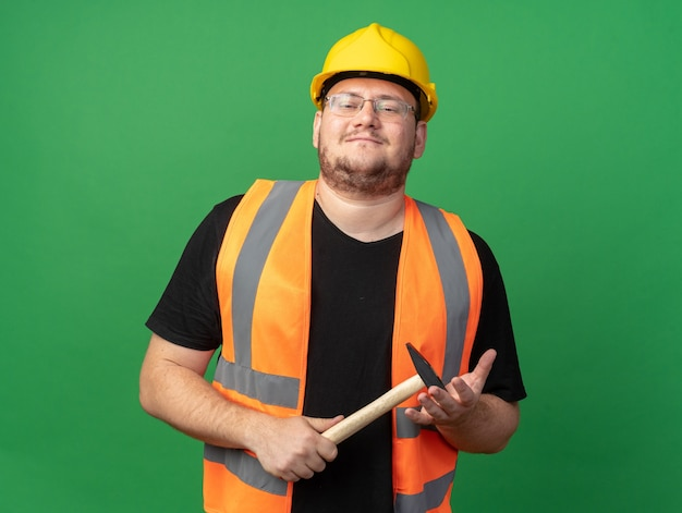 Gelukkig bouwer man in bouw vest en veiligheidshelm met hamer kijken camera glimlachend zelfverzekerd staande over groene achtergrond