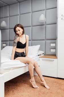 Gelukkig bruette vrouw in sexy zwarte pyjama zit op de rand van het bed in haar lichte kamer