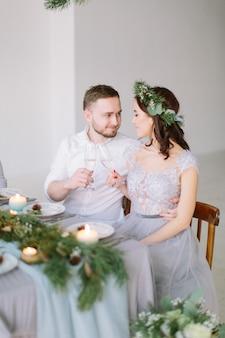 Gelukkig bruidsmeisje en groomman glimlachend en knuffelen aan de bruiloft tafel