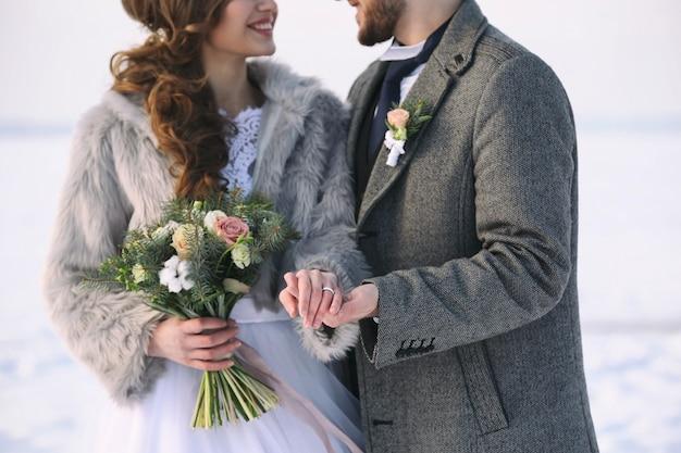 Gelukkig bruidspaar buitenshuis op winterdag