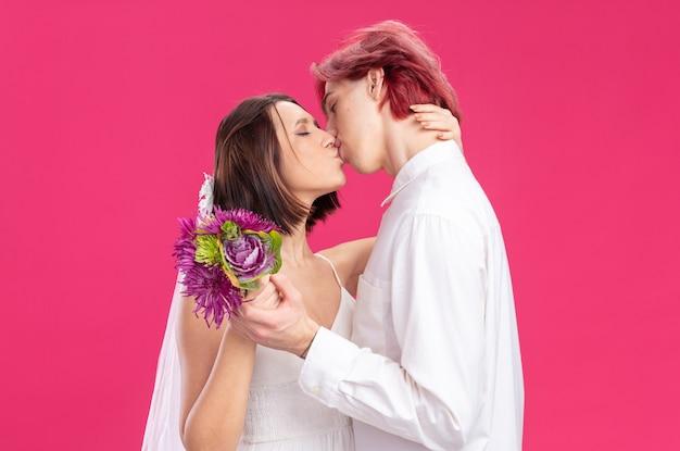 Gelukkig bruidspaar in trouwjurk met bloemen gelukkig verliefd omhelzen en kussen staande over roze muur
