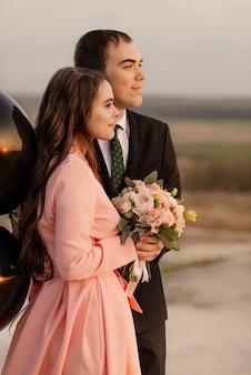 Gelukkig bruidspaar lopen op prachtig landschap bij zonsondergang met grote helium ballonnen. bruiloft concept.