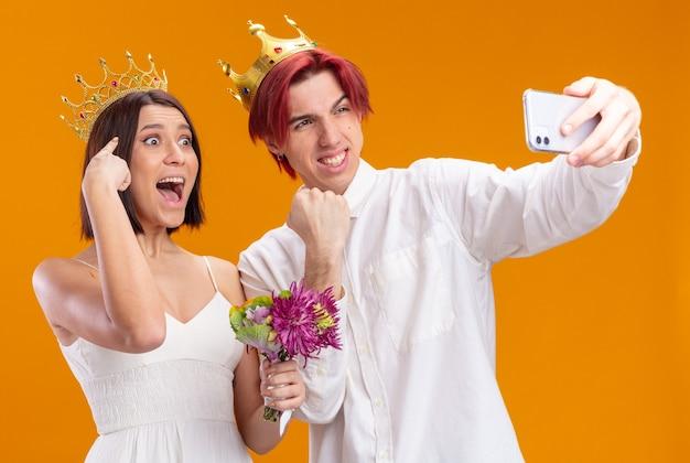 Gelukkig bruidspaar met boeket bloemen in trouwjurk met gouden kronen glimlachend vrolijk doend selfie met smartphone staande over oranje muur