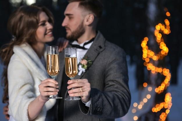 Gelukkig bruidspaar met glazen champagne op winteravond