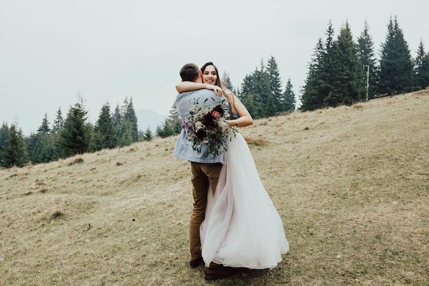 Gelukkig bruidspaar, pasgetrouwde vrouw en man omarmen in groen bos.