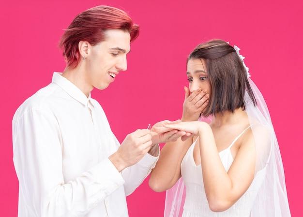 Gelukkig bruidspaar van bruidegom en bruid, gelukkige bruidegom die een trouwring aan de vinger van zijn opgewonden bruid zet die over roze muur staat