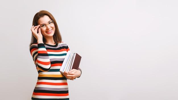 Gelukkig bruinharige vrouw met bril in een veelkleurige jurk houdt boeken in haar handen, kijkt naar de camera en glimlacht