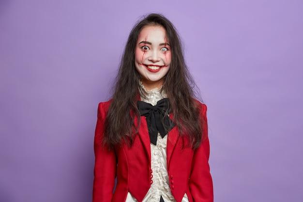 Gelukkig brunette angstaanjagende aziatische vrouw heeft griezelige ogen met lenzen en bloedlittekens gekleed in maskeradekostuum glimlacht positief geïsoleerd op levendige paarse muur