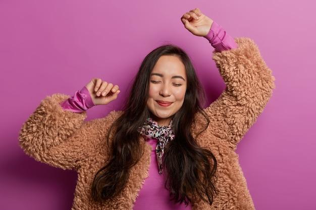 Gelukkig brunette aziatische vrouw danst, spreidt handen in de lucht, geniet van muziek, maakt coole bewegingen, nodigt uit om mee te dansen met haar, heeft een romantische sfeer, een tedere blik