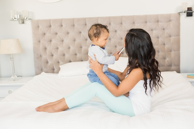 Gelukkig brunette die haar baby houden die smartphone op bed houdt