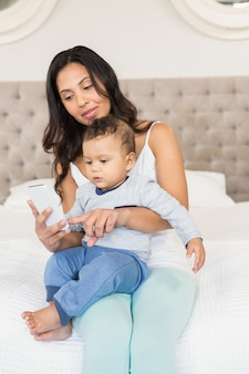 Gelukkig brunette die haar baby houden en smartphone in slaapkamer gebruiken