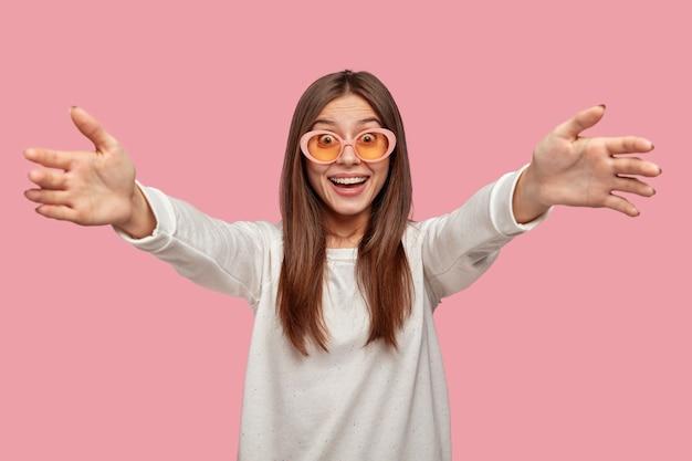Gelukkig brunette jonge vrouw toont welkom gebaar, spreidt handen als beste vriend wil knuffelen, glimlacht breed, draagt witte trui en zonnebril, geïsoleerd over roze muur. kom naar me toe!