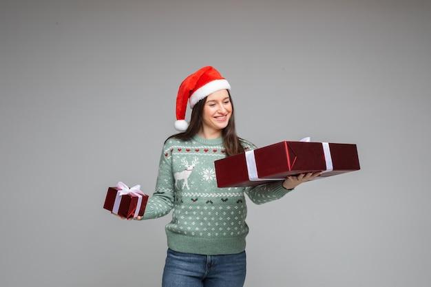 Gelukkig brunette kerstmeisje in warme wintertrui met kerst- en nieuwjaarsgeschenken op grijze achtergrond met kopieerruimte