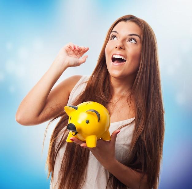 Gelukkig brunette meisje houdt biggetje spaarpot.