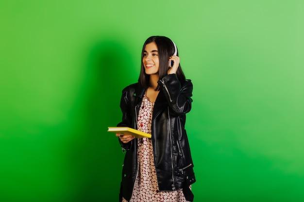 Gelukkig brunette meisje met koptelefoon houdt een gele notebook in haar hand en lacht zoet.