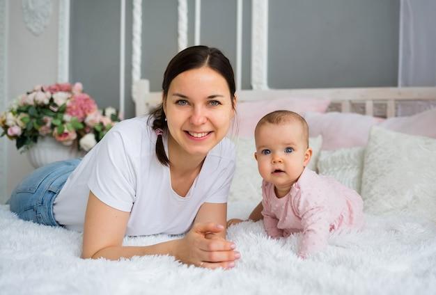 Gelukkig brunette moeder met haar dochter ligt op het bed in de kamer en kijkt naar de camera