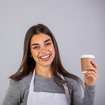 Gelukkig brunette serveerster in schort biedt u glas met hete koffie terwijl u geïsoleerd voor de camera staat.