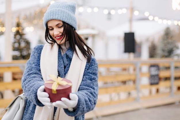 Gelukkig brunette vrouw draagt gebreide muts en blauwe jas met rode geschenkdoos op de kerstmarkt. ruimte voor tekst
