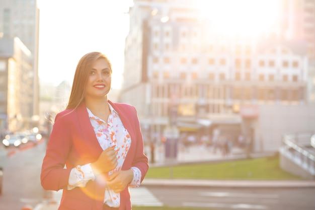 Gelukkig brunette vrouw dragen blouse en roze jas poseren op de achtergrond van de stad van de avond. ruimte voor tekst