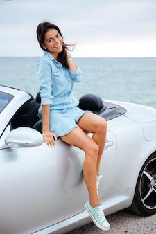 Gelukkig brunette vrouw en haar nieuwe auto op het strand