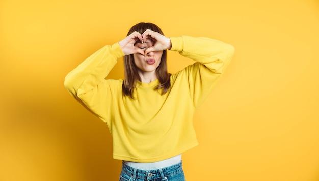 Gelukkig brunette vrouw hartsymbool met handen poseren geïsoleerd op heldere gele achtergrond maken