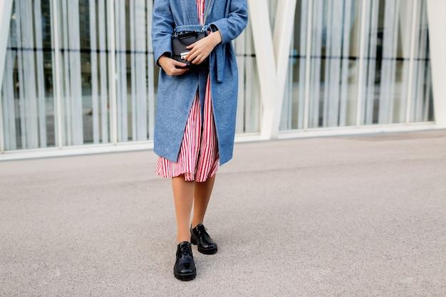 Gelukkig brunette vrouw in blauwe jas en rode jurk wandelen langs moderne straat