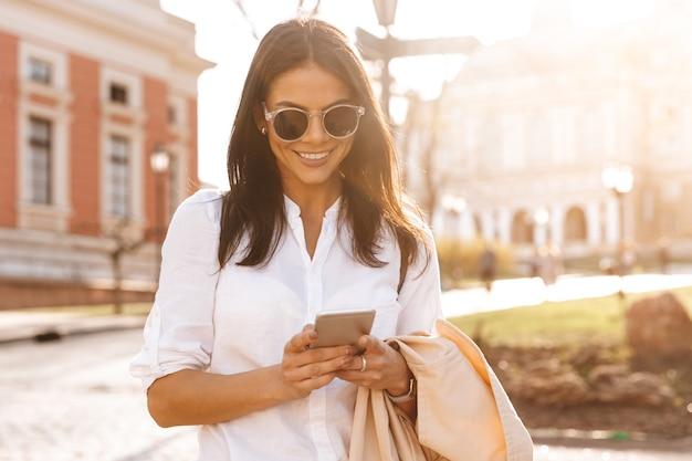 Gelukkig brunette vrouw in shirt en zonnebril bericht schrijven