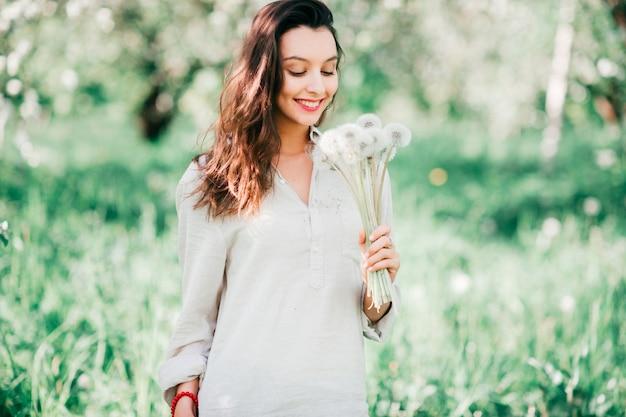 Gelukkig brunette vrouw in wit overhemd in bloeiende lentetuin met boeket van paardebloemen.
