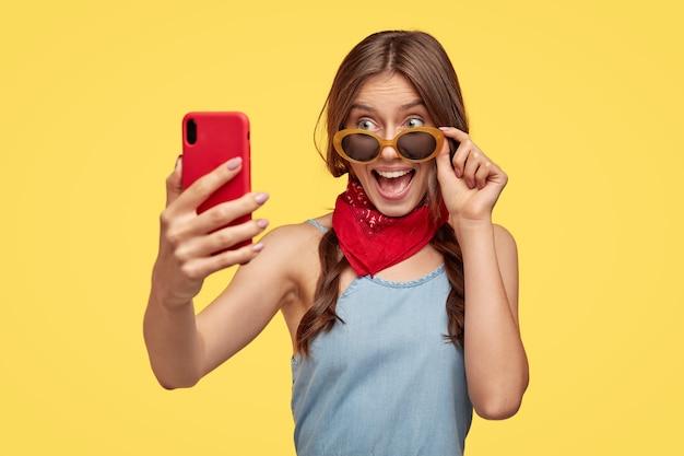 Gelukkig brunette vrouw met vrolijke blik, verheugt zich het kopen van stijlvolle tinten voor de zomer, bereidt zich voor op vakantie, maakt foto van zichzelf op mobiel, modellen tegen gele muur. meisje neemt selfie