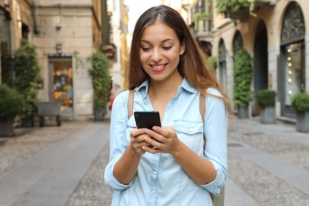Gelukkig brunette vrouw sms typen op smartphone in stad