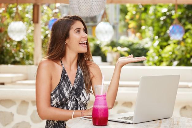 Gelukkig brunette vrouwelijke copywriter maakt externe baan, maakt gebruik van laptopcomputer