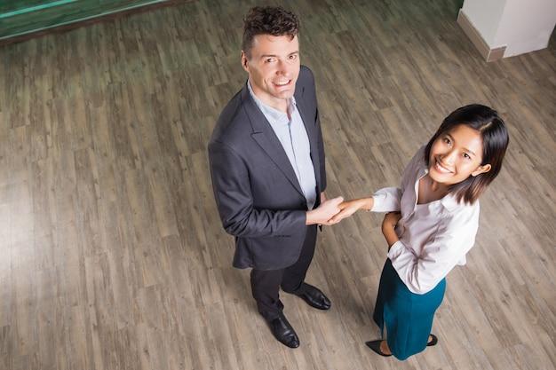 Gelukkig business man en vrouw handen schudden in hall