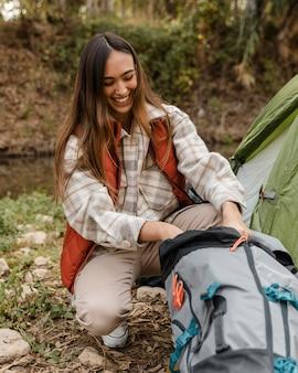 Gelukkig camping meisje in het bos op zoek naar rugzak