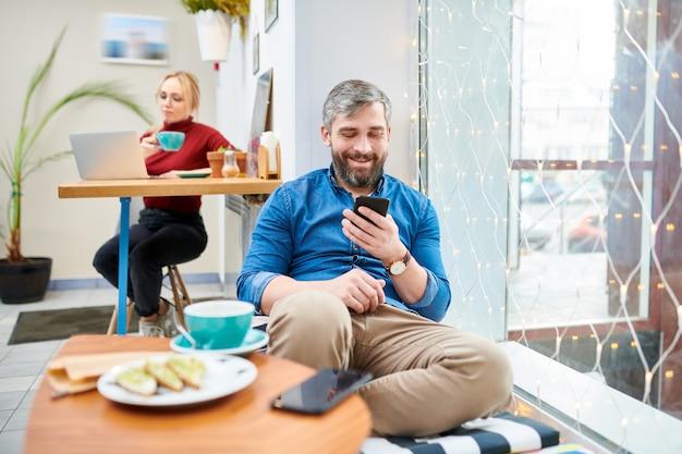 Gelukkig casual jongeman ontspannen in café terwijl scrollen in smartphone of messaging naar iemand