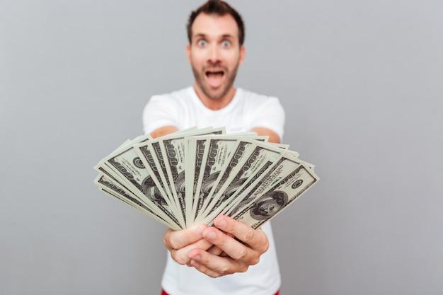 Gelukkig casual man die geld op camera geeft over grijze achtergrond