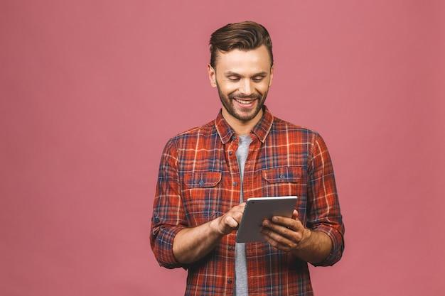 Gelukkig casual man met behulp van tablet-computer geïsoleerd op een roze achtergrond