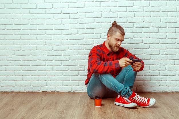 Gelukkig casual man zittend op de vloer