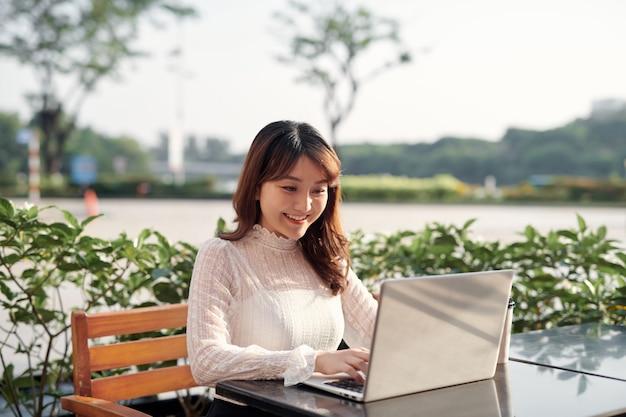 Gelukkig casual mooie vrouw met behulp van laptop zittend in een coffeeshop buiten op een zonnige dag